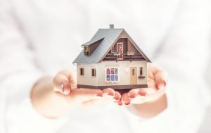 Hands,Of,Young,Woman,Holding,Model,House,,Real,Estate,Insurance